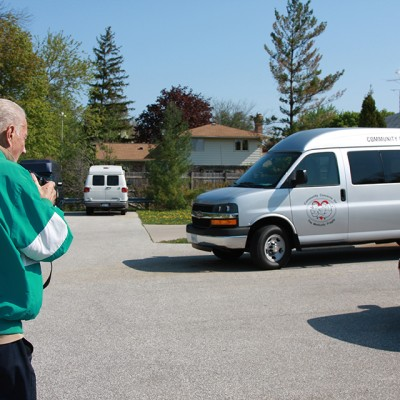 Norman Alix taking a picture of the new van for the Community Concerns for the Medically Fragile